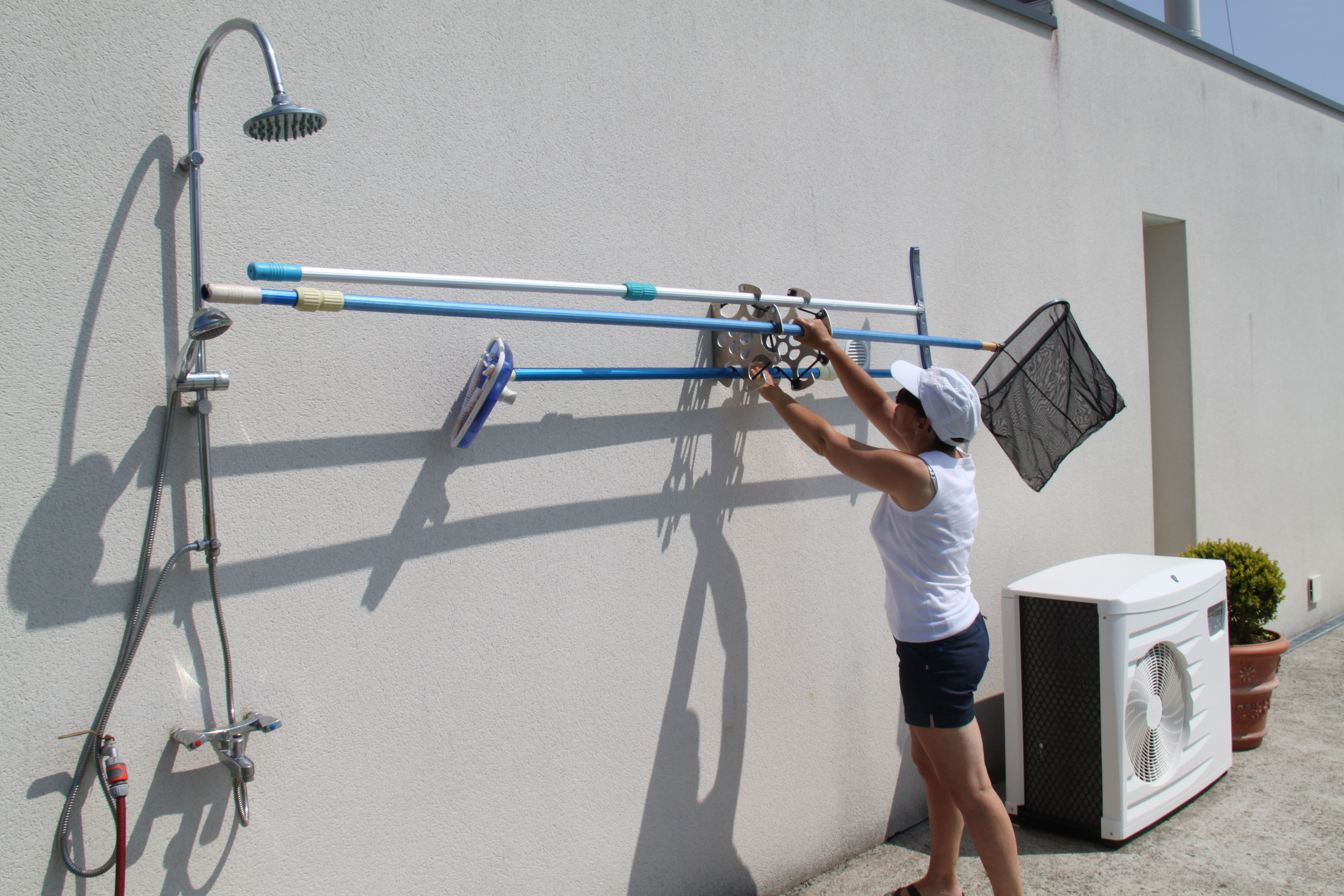 Prise en main d'une épuisette sur le support de rangement du matériel de nettoyage de piscines